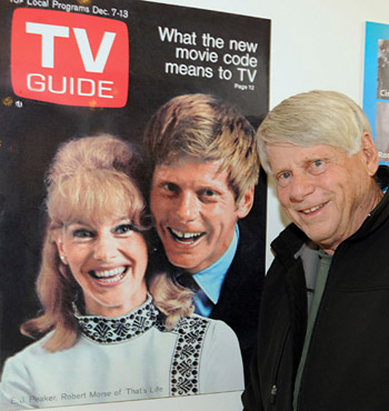 Robert Morse poses next to a 1968 cover of <i>TV Guide</i> featuring himself and <i>That's Life</i> co-star E.J. Peaker. (Photo courtesy of the Paley Center for Media.)